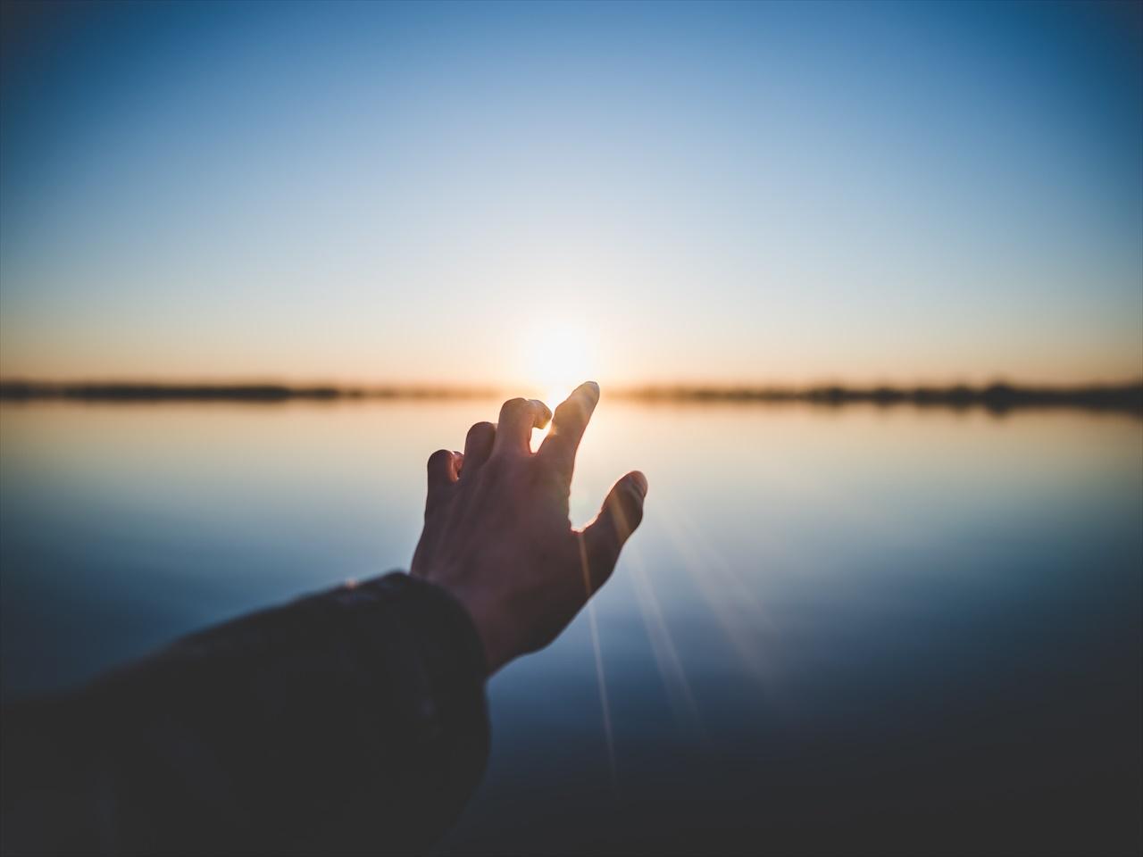 夕日が沈む地平線に手を伸ばす人