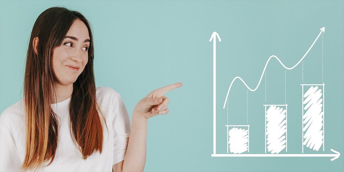 上昇トレンドのグラフを指さす女性