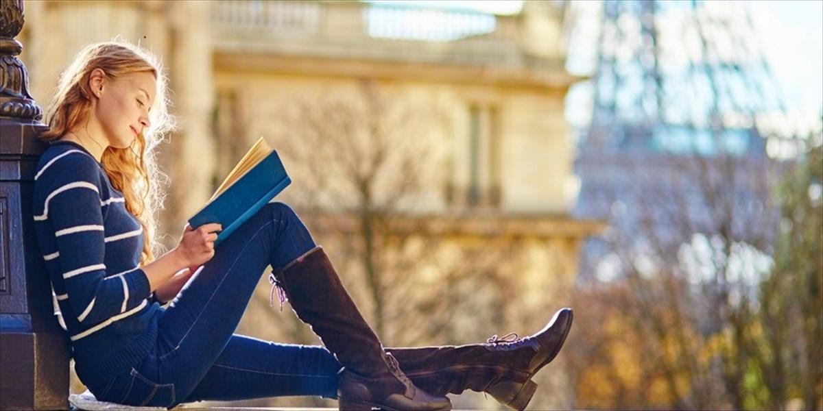 塀の上で座って本を読む女性